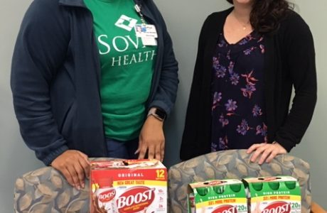 two ladies pose with supply of donated Boost